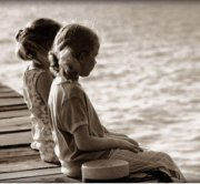 two young girls sitting on a dock