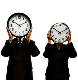 Workers holding clocks in front of their faces