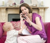working  mom on couch with toddler