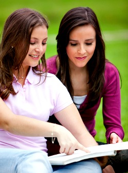 two teen girls reading a book