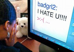 teenager in front of computer with bullying message