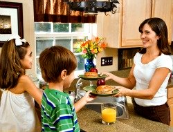 mom serving breakfast to son and daughter