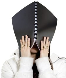 stressed female with notebook covering face